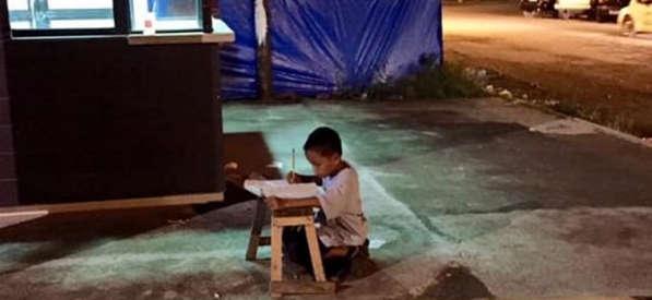 Foto simbolo, il bambino studia alla luce del lampione